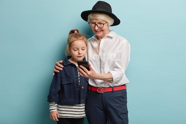 Familie-, generatie- en technologieconcept. gelukkig modieuze grootmoeder houdt smartphone vast, omhelst vrouwelijk kleinkind, bekijk video samen, hebben lekker samen thuis, poseren over blauwe muur