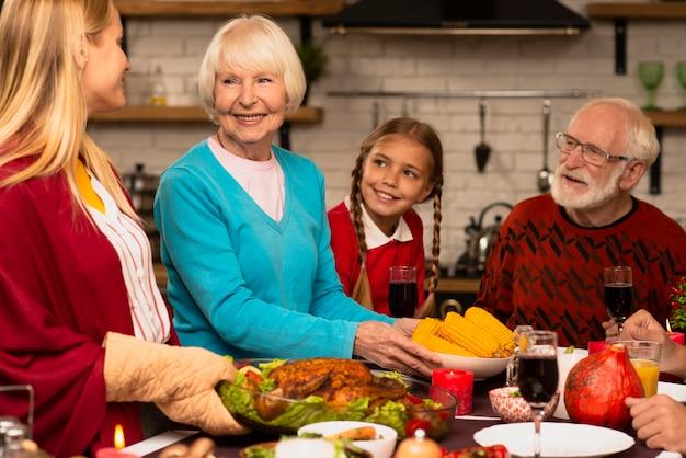 Familie generaties kijken naar de moeder die de kalkoen brengt