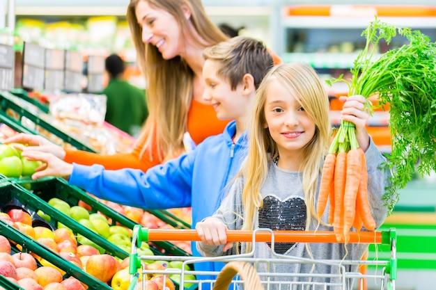 Familie groenten en fruit selecteren tijdens het boodschappen doen in de supermarkt