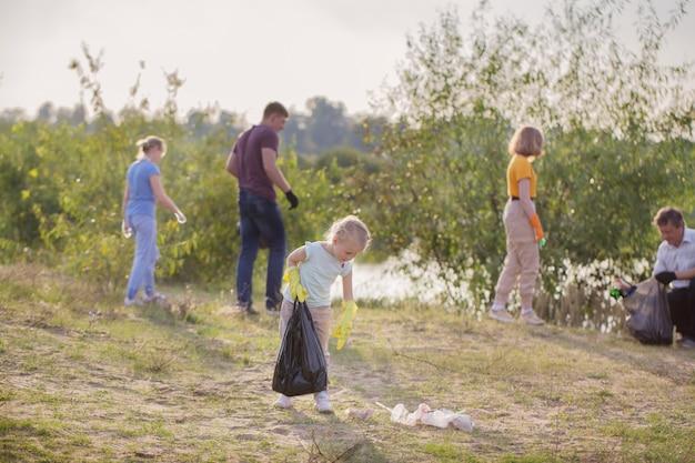 Familie haalt afval op het strand in de zomer