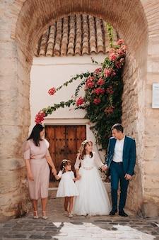 Familie hand in hand terwijl ze gelukkig zijn omdat hun oudste dochter de communie heeft gedaan