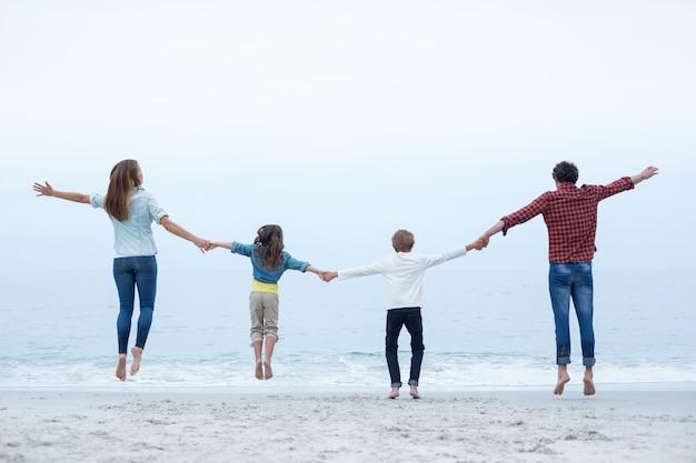 Familie hand in hand tijdens het springen op zee kust