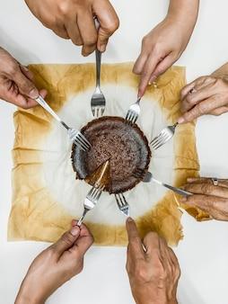 Familie handen met vork chocolade cheesecake eten.