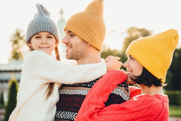 Familie heeft een onvergetelijke tijd samen, omhelzen elkaar, draag trendy gebreide hoeden