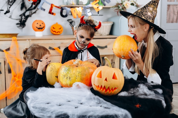 Familie heeft grappige tijd thuis. moeder en dochter die een pompoen halloween gaan bijten