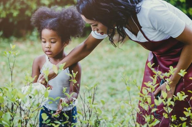 Familie heerlijk tuinieren en groene plantactiviteit water geven met kinderen tijdens stay at home om de uitbraak van het coronavirus te verminderen. kinderen die de plant water geven in de achtertuin.