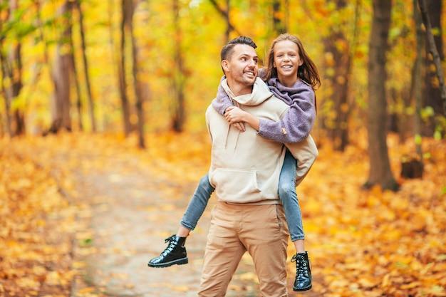 Familie herfstdag. jonge vader en zijn dochtertje samen in de herfstpark
