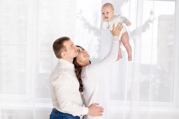 Familie, het concept van een gelukkig jong gezin met een klein kind, vader, moeder en dochter die thuis bij het raam knuffelen