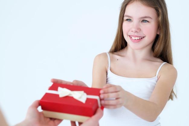 Familie houdt van zorg en waardering. moeder die een geschenk geeft aan haar kleine meisje.