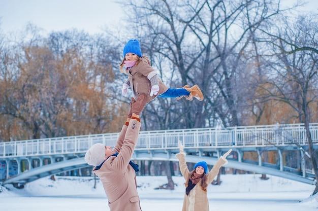 Familie in beige en blauwe kleren met plezier op het bevroren meer in het park tegen de achtergrond van de brug