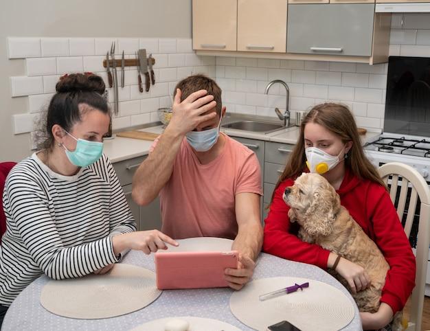 Familie in beschermende maskers kijken naar schokkend nieuws op een tablet thuis