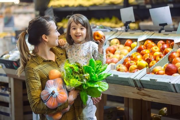 Familie in de supermarkt. mooie jonge moeder en haar dochtertje glimlachend en eten kopen. het concept van gezond eten. oogst