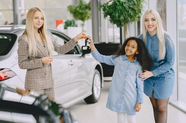 Familie in een autosalon. vrouw die de auto koopt. weinig afrikaans meisje met mther. manager met klanten.