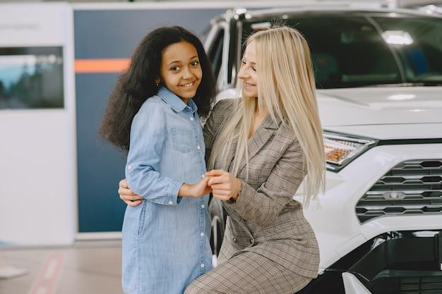 Familie in een autosalon. vrouw die de auto koopt. weinig afrikaans meisje met mther.