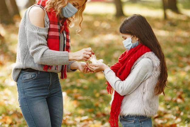 Familie in een herfstpark. coronavirus-thema. moeder met dochter. mensen gebruiken antiseptica.