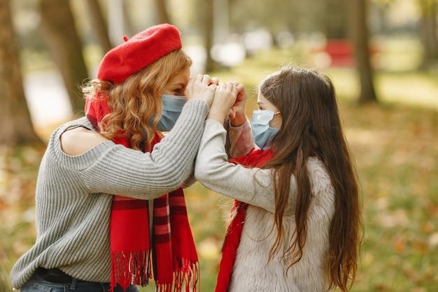 Familie in een herfstpark. coronavirus-thema. moeder met dochter.