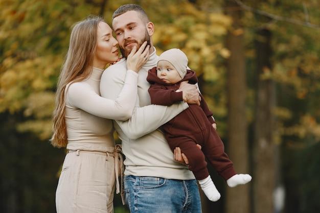 Familie in een herfstpark. man in een bruine trui. leuk meisje met ouders.