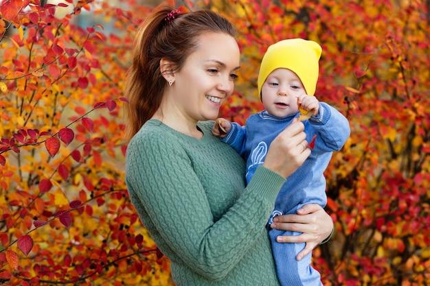 Familie in een herfstpark moeder in een groene trui schattig klein meisje