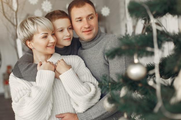 Familie in een kamer. weinig jongen dichtbij kerstmisdecoratie. moeder met vader met zoon