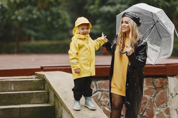 Familie in een regenachtig park. kid in een gele regenjassen en vrouw in een zwarte jas.