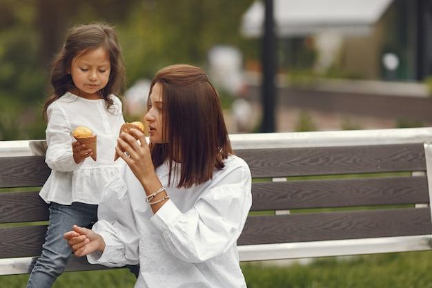 Familie in een stad. klein meisje eet ijs. moeder met dochter zittend op een bankje.