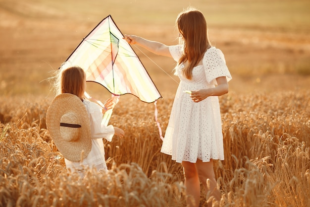 Familie in een tarweveld. vrouw in een witte jurk. klein kind met vlieger.