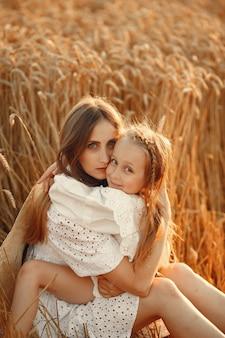 Familie in een tarweveld. vrouw in een witte jurk. meisje met strohoed.