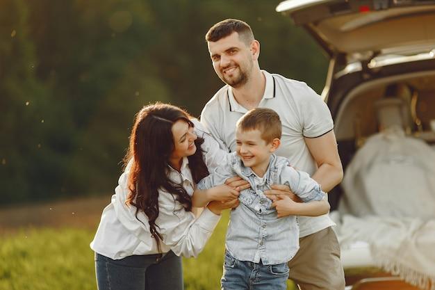 Familie in een zomer bos door de open stam