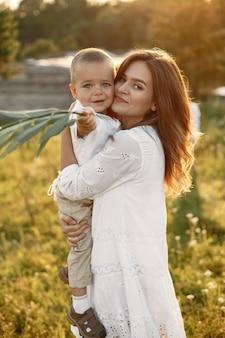 Familie in een zomerpark. moeder in een witte jurk. schattige kleine jongen