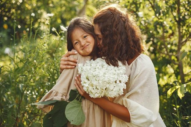 Familie in een zomertuin. sensuele foto. schattig klein meisje. vrouw met boeket.