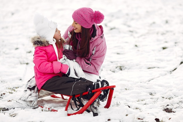 Familie in gebreide wintermutsen op familiekerstvakantie. vrouw en meisje in een park. mensen spelen met slee.