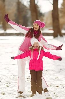 Familie in gebreide wintermutsen op familiekerstvakantie. vrouw en meisje in een park. mensen spelen.