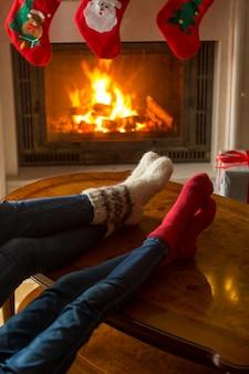 Familie in gebreide wollen sokken die opwarmen bij brandende open haard in huis