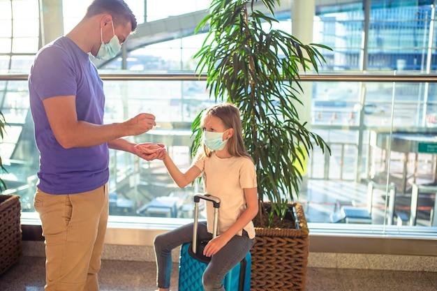 Familie in gezichtsmasker in luchthaven. handdesinfecterend middel op openbare plaatsen ter bescherming tegen virussen en ziekten
