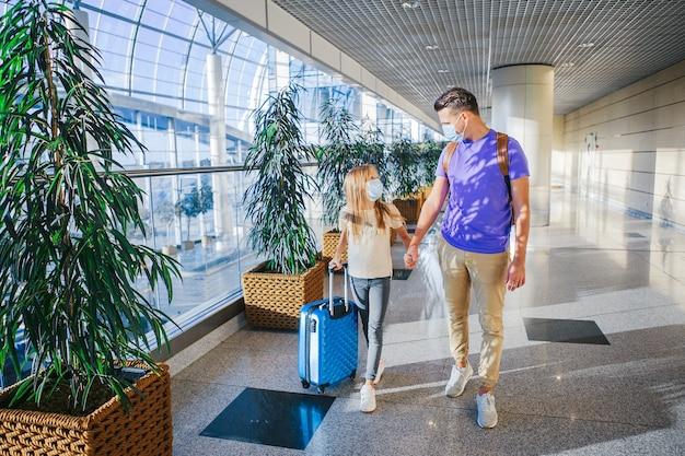 Familie in gezichtsmasker in luchthaven. vader en kind dragen gezichtsmasker tijdens uitbraak van coronavirus en griep