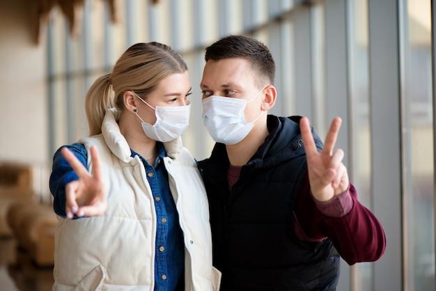 Familie in gezichtsmasker in winkelcentrum of luchthaven. paar dragen gezichtsmasker tijdens coronavirus en griepuitbraak. bescherming tegen virussen en ziekten op een openbare, drukke plaats.