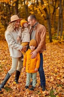 Familie in herfst bos, samen vrije tijd buiten doorbrengen in frisse lucht