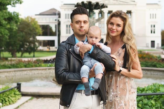 Familie in het stadspark. jong gelukkig paar met de kleine babyjongen