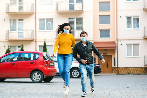 Familie in medische masker buiten huis. coronavirus quarantaine. mensen hebben een gezichtsmasker nodig in de openbare ruimte. wereldwijde pandemie.