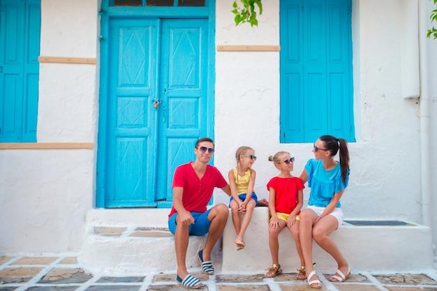 Familie in mykonos op zomervakantie. ouders en kinderen op smalle straat in traditioneel grieks dorp