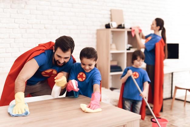 Familie in pakken van superhelden wordt thuis schoongemaakt.