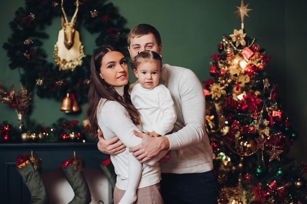 Familie in presenteert naast kerstboom.