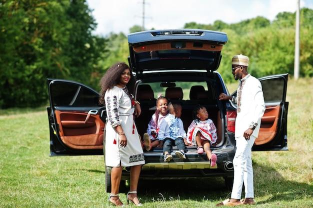 Familie in traditionele kleding staan tegen hun auto, kinderen zitten op de kofferbak