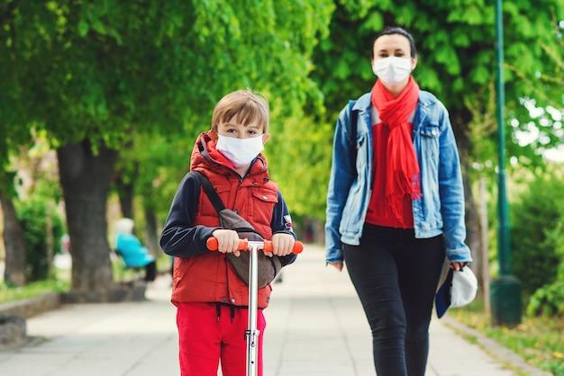 Familie in veiligheidsmaskers buitenshuis. rijdende jongen op autoped in park. jongen draagt medische gezichtsmasker. corona-epidemie.