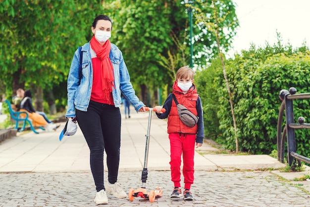 Familie in veiligheidsmaskers buitenshuis. rijdende jongen op autoped in park. jongen draagt medische gezichtsmasker.