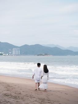Familie in witte kleren lopen op het strand