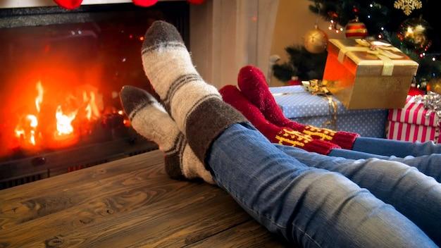 Familie in wollen sokken ontspannen bij de open haard in de kamer die is ingericht voor kerstmis