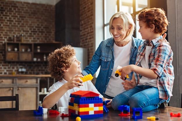 Familie is een klein woord gecreëerd door liefde. positief ingestelde grootmoeder kijkt naar haar kleinkinderen met ogen vol liefde terwijl ze hen omhelst