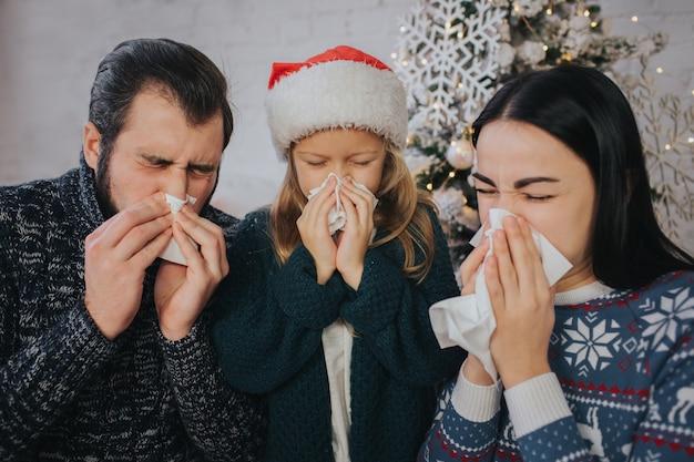 Familie is ziek met kerstmis. ze hebben een zakdoek. zieke mensen hebben een loopneus. vrolijk kerstfeest en een gelukkig nieuwjaar