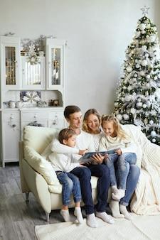 Familie, jeugd, vakanties en mensen - glimlachende moeder, vader en kleine kinderen die een boek lezen over de achtergrond van de lichten
